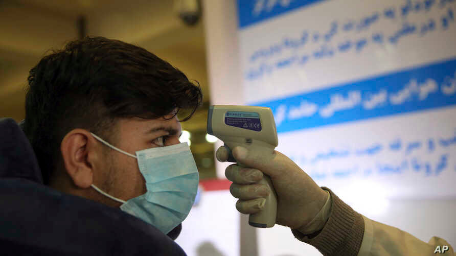 An Afghan health worker takes the temperature of a passenger as a preventive measure for Coronavirus, during screening of…