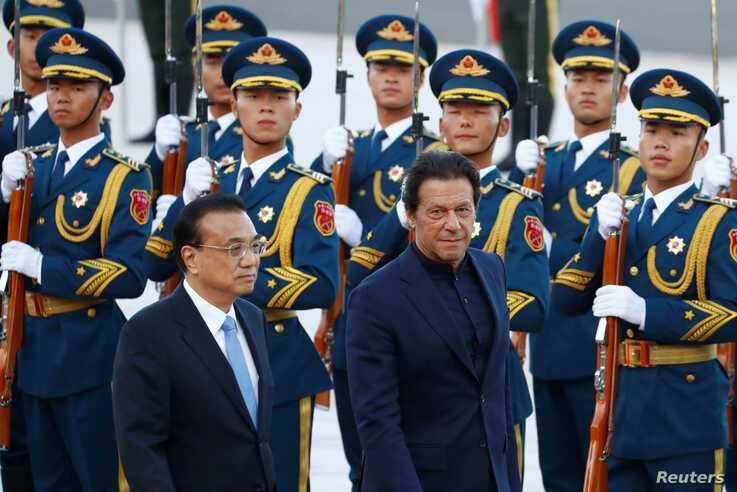 Pakistan's Prime Minister Imran Khan reviews the honour guard during a welcome ceremony with Chinese Premier Li Keqiang outside…